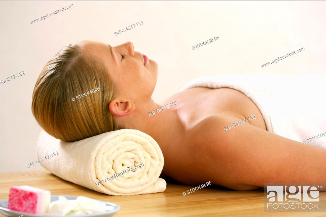 Stock Photo: Young woman wrapped in a towel relaxing.