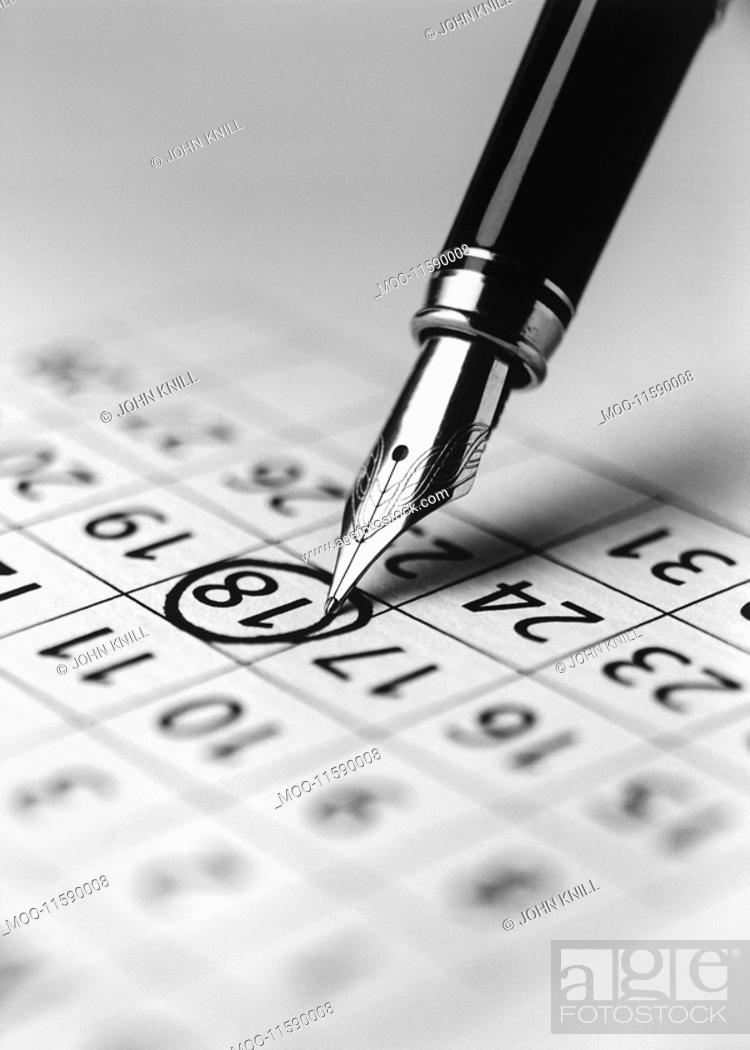 Stock Photo: Tip of fountain pen marking date in calendar b&w close-up.