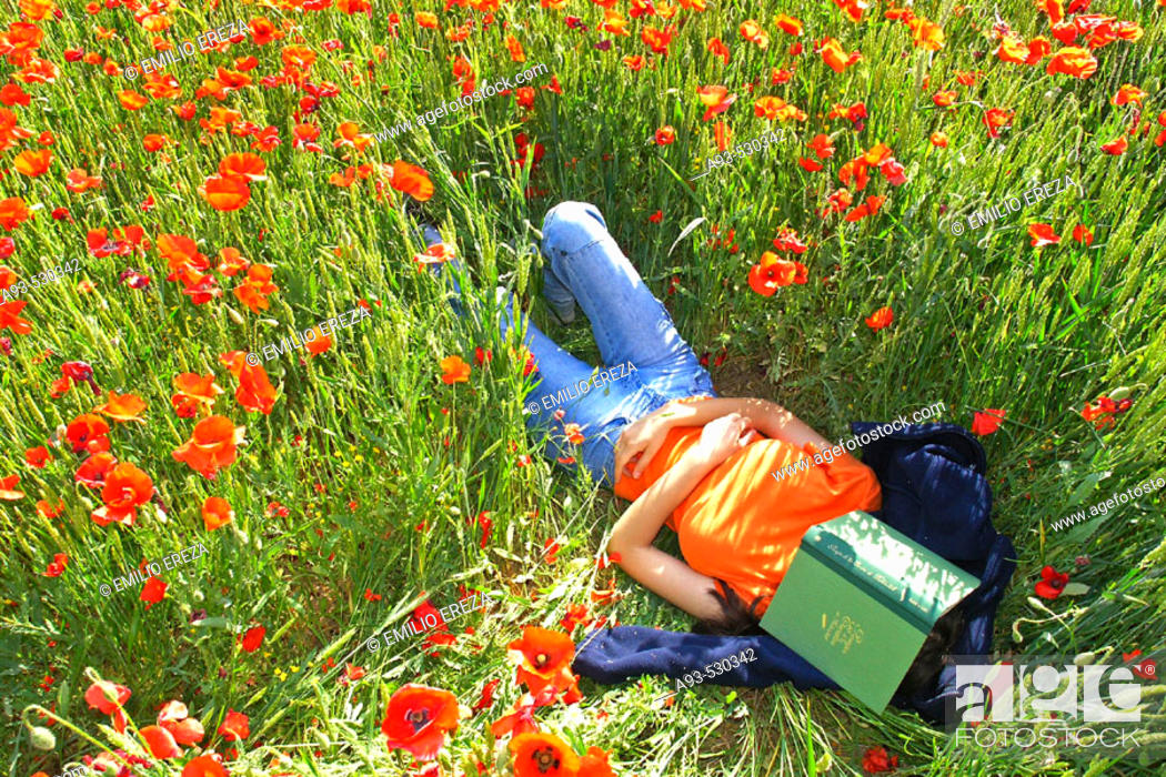 Stock Photo: Woman lying on a poppies field.