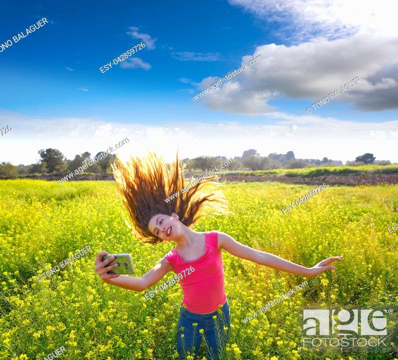 Photo de stock: Teen girl selfie video photo in spring meadow moving hair.