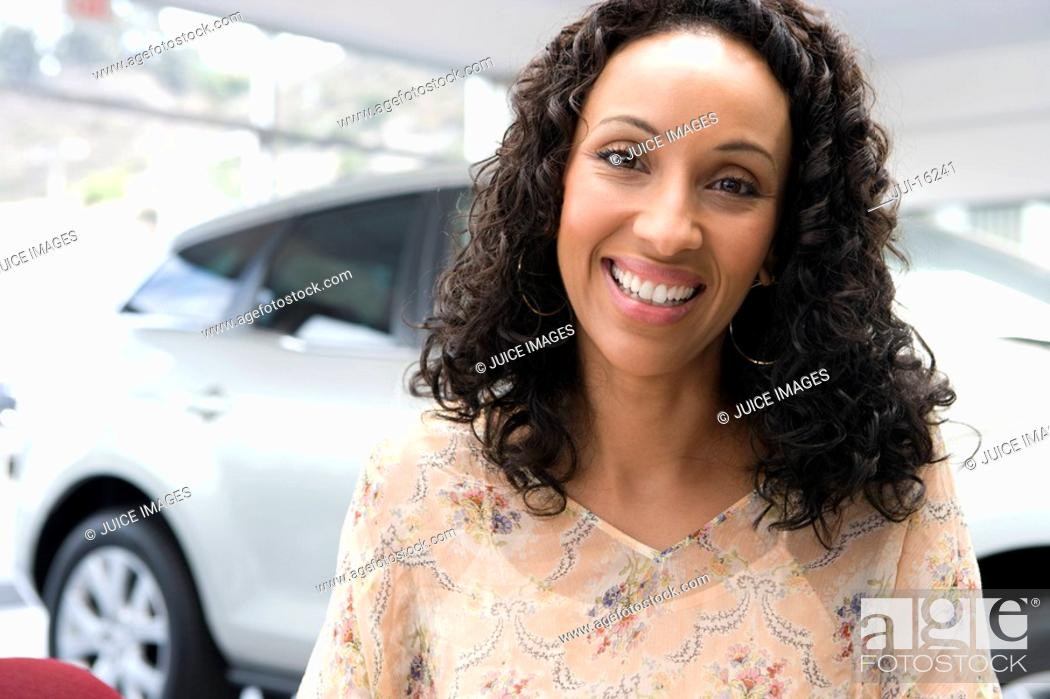 Stock Photo: woman smiling in car showroom.