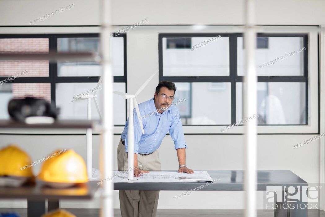 Man with blueprint and wind turbine models in office, Stock