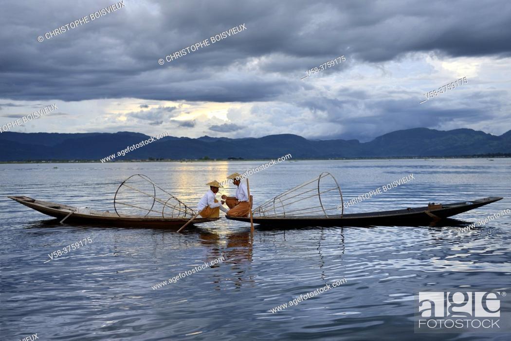 Stock Photo: Myanmar, Shan State, Inle Lake, Intha fishermen lighting a cigar.