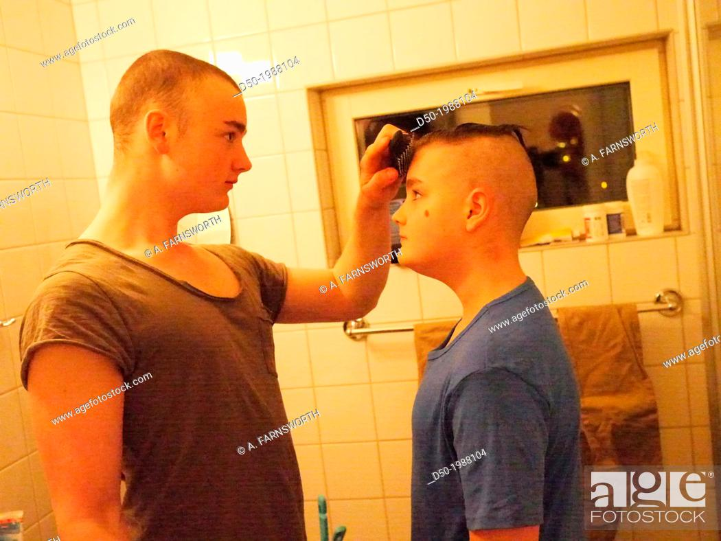 Stock Photo: 16 year old giving a haircut to his 12 year old brother. Stockholm, Sweden.