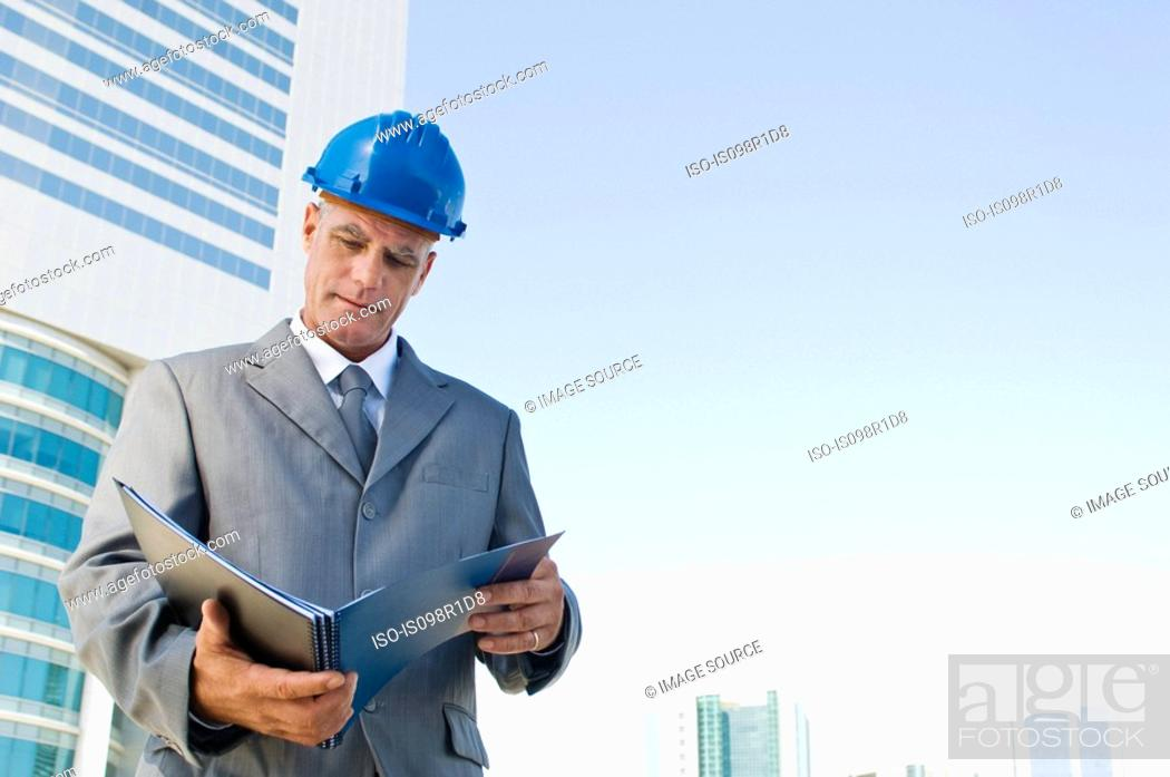 Stock Photo: An architect reading a book.