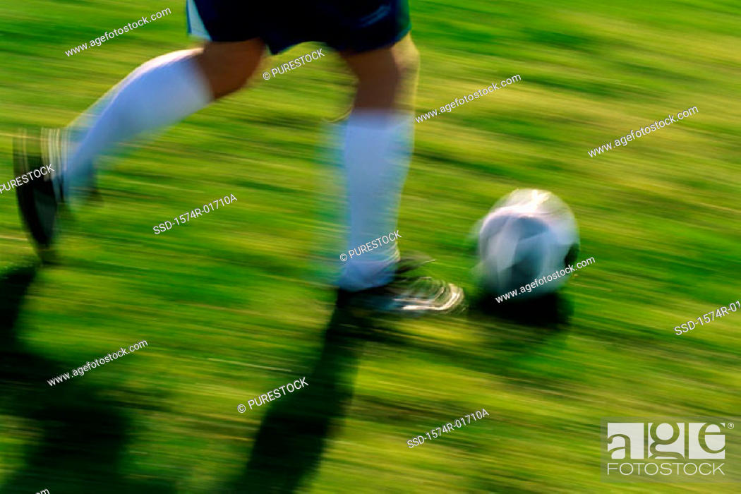 Stock Photo: Low section view of a soccer player running with the ball.