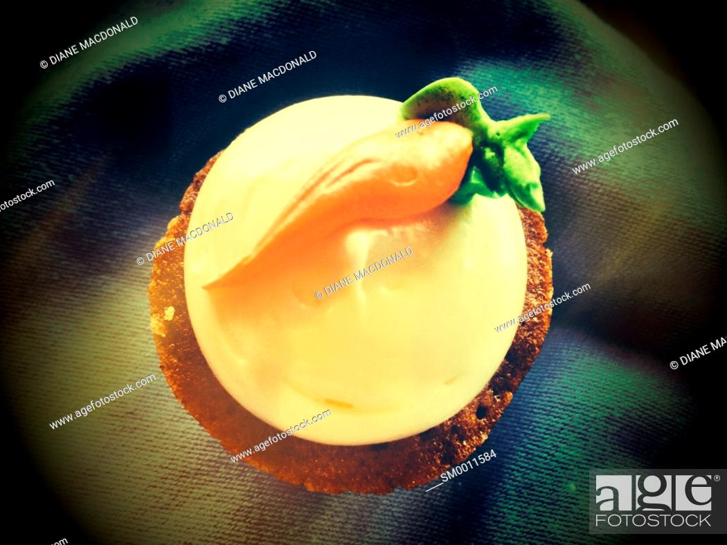 Stock Photo: A carrot muffin with a carrot shape on the icing or frosting.