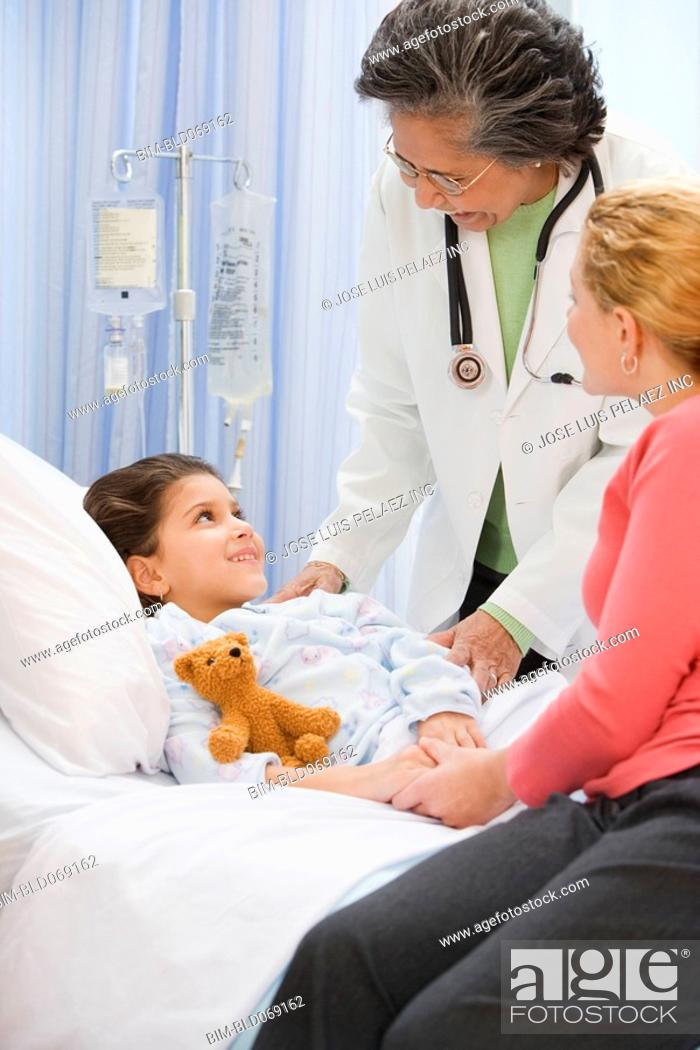 Stock Photo: Senior female doctor talking to girl in hospital bed.