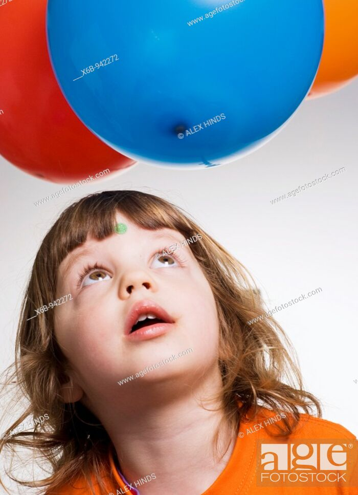 Stock Photo: Young girl, three years old, looking up at balloons.