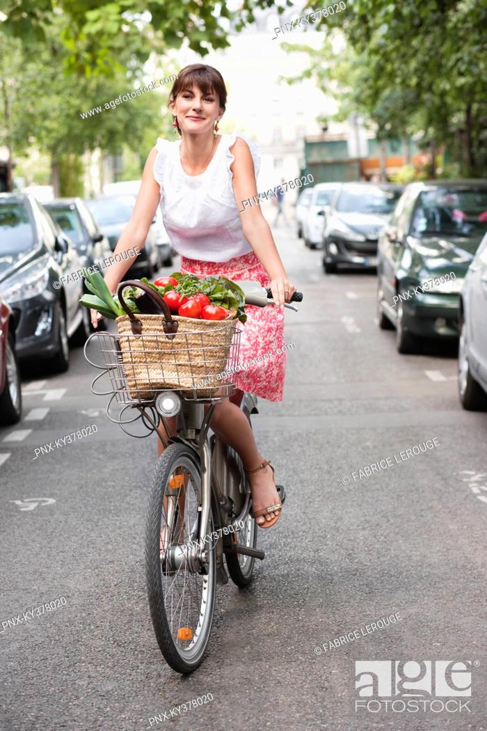 Stock Photo: Woman carrying vegetables on a bicycle, Paris, Ile-de-France, France.