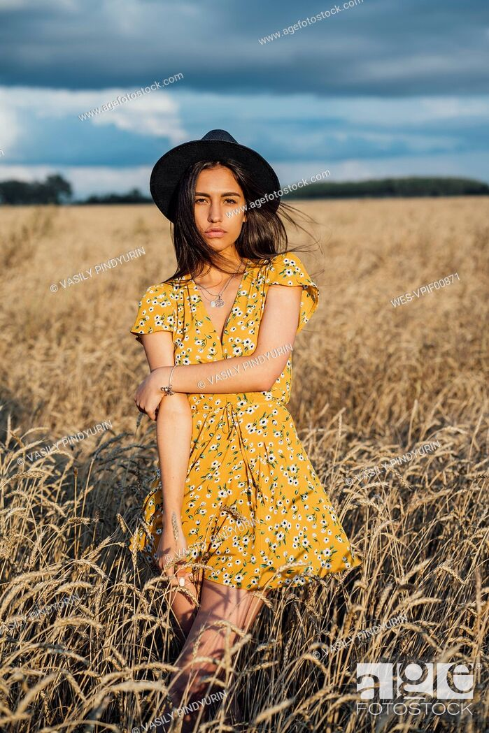 Stock Photo: Portrait of young woman wearing summer dress with floral design and a hat dancing in corn field.