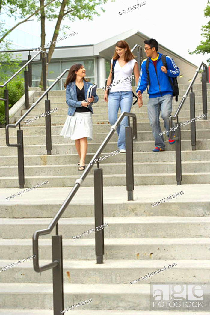 Stock Photo: Low angle view of three college students moving down a staircase and smiling.