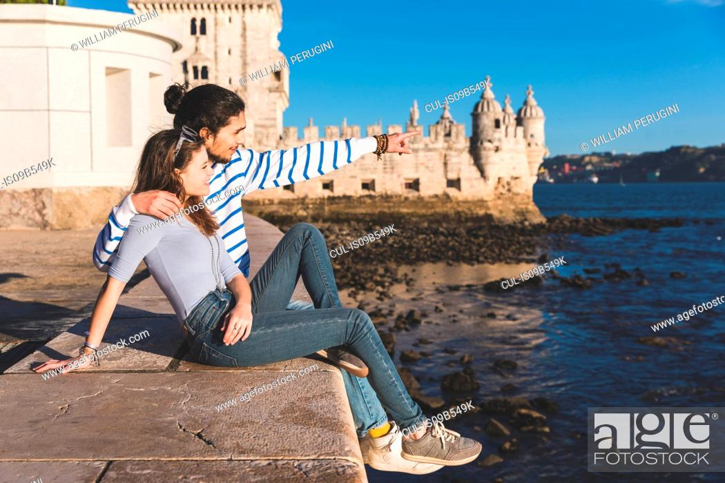 Stock Photo: Young couple sitting on wall by sea, Belem Tower in background, looking at view.