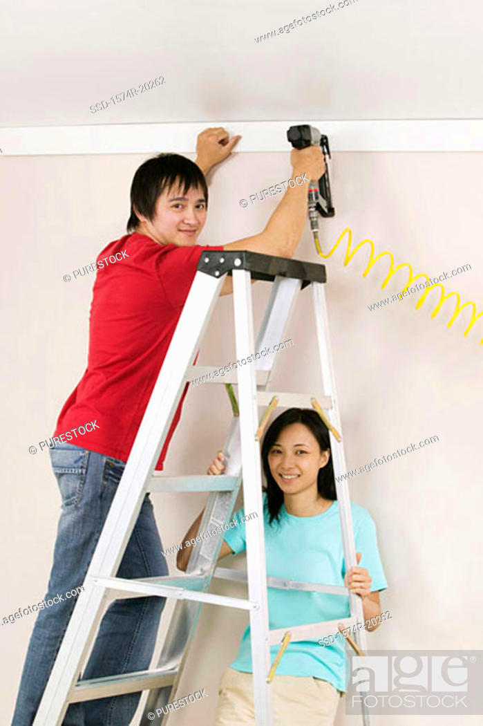 Stock Photo: Portrait of a young man using a drill on a wall with a young woman holding a ladder.