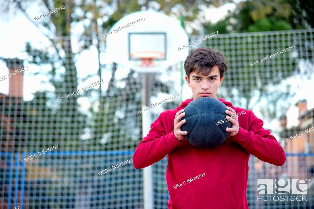 Photo de stock: Teenager holding basketball and looking on camera.