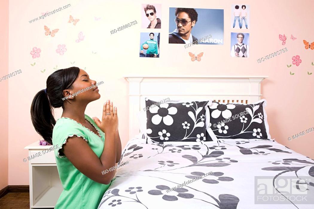 Stock Photo: Girl praying in her bedroom.