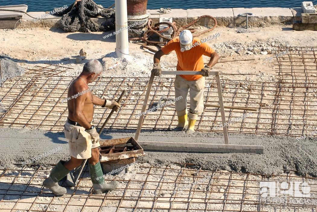 Stock Photo: Gallipoli Italy: workers pouring concrete at the port docks.
