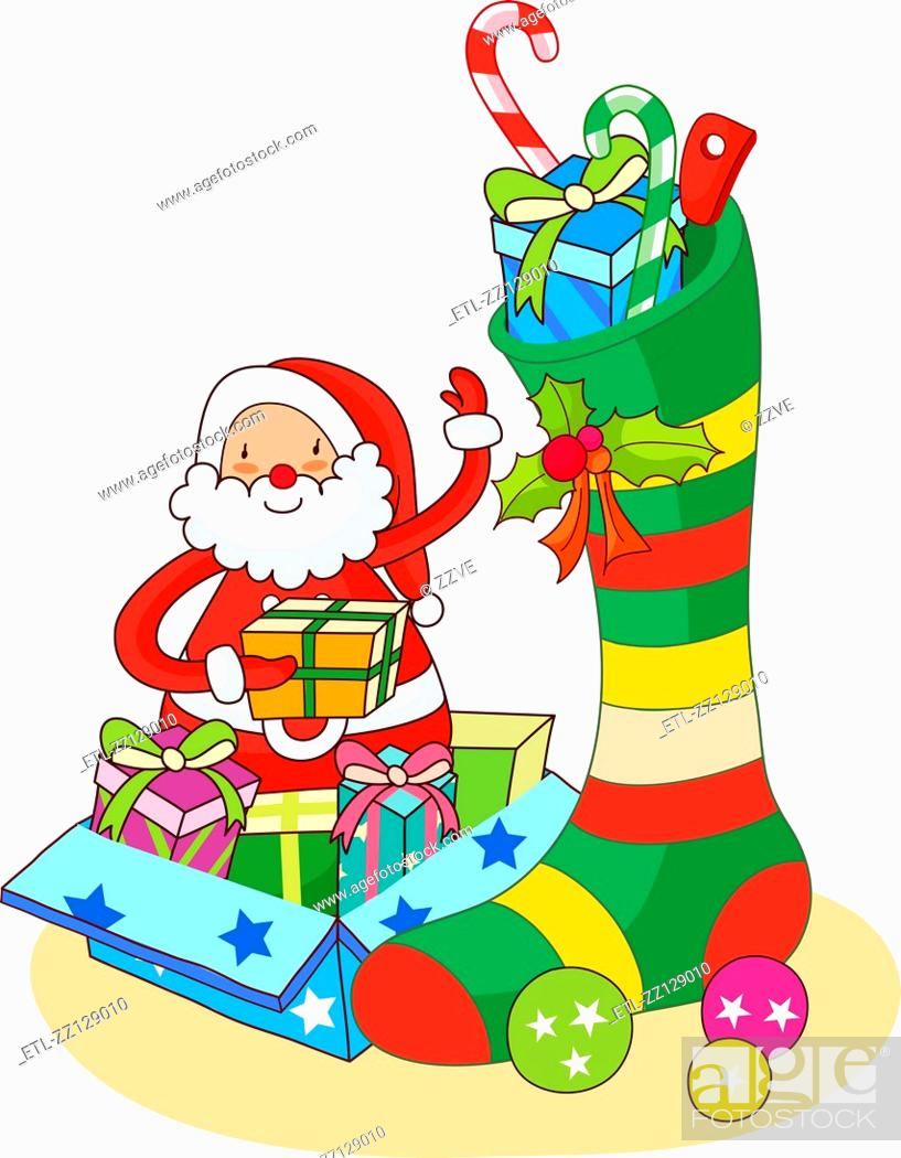 Stock Photo: Santa Claus putting Christmas presents in a Christmas stocking.