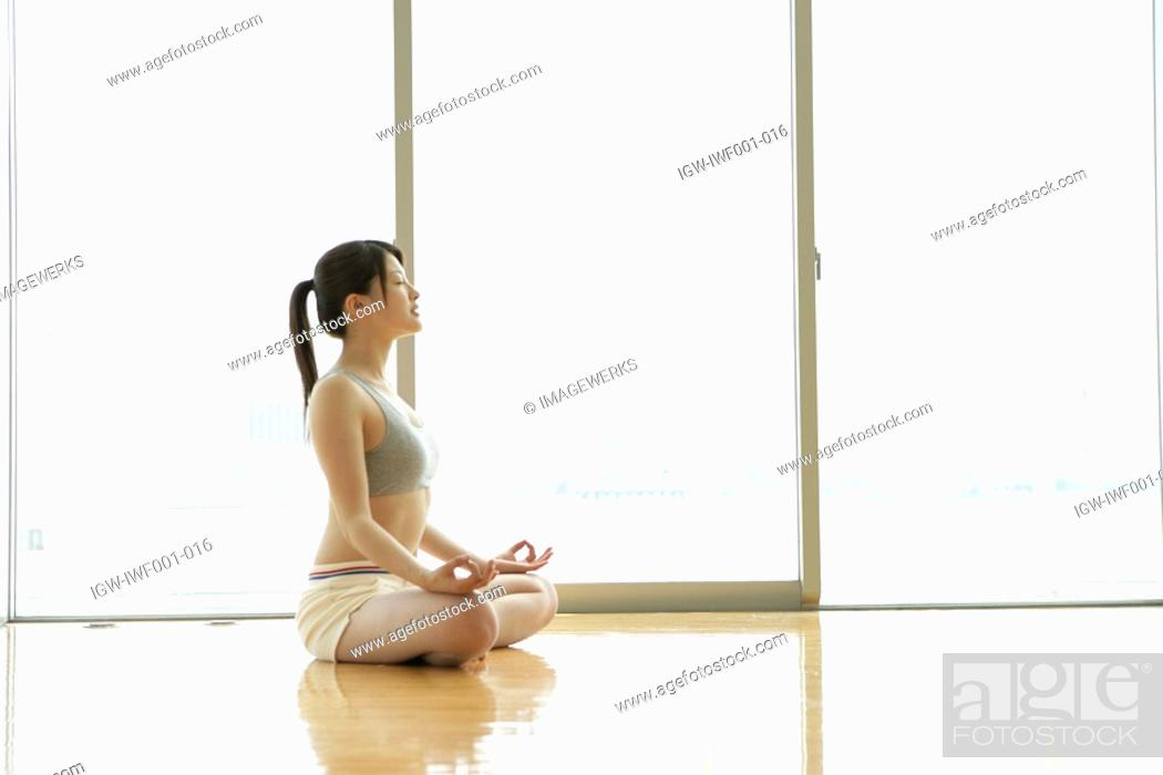Stock Photo: A young woman in deep meditation while doing yoga in the gym.