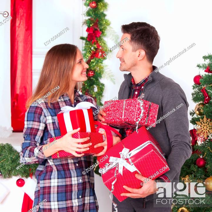 Stock Photo: Couple in love sitting next to a nicely decorated Christmas tree, hloding Christmas gifts and smiling.