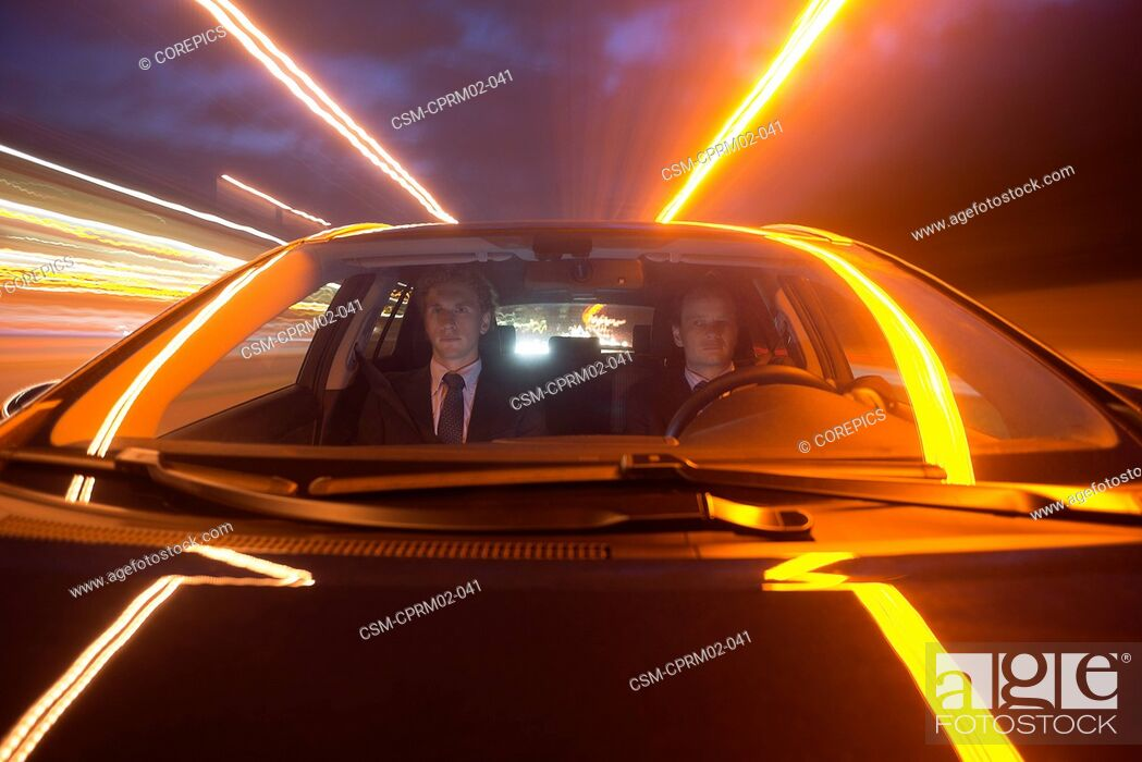 Stock Photo: Two businessmen driving in a car over a motorway at night.