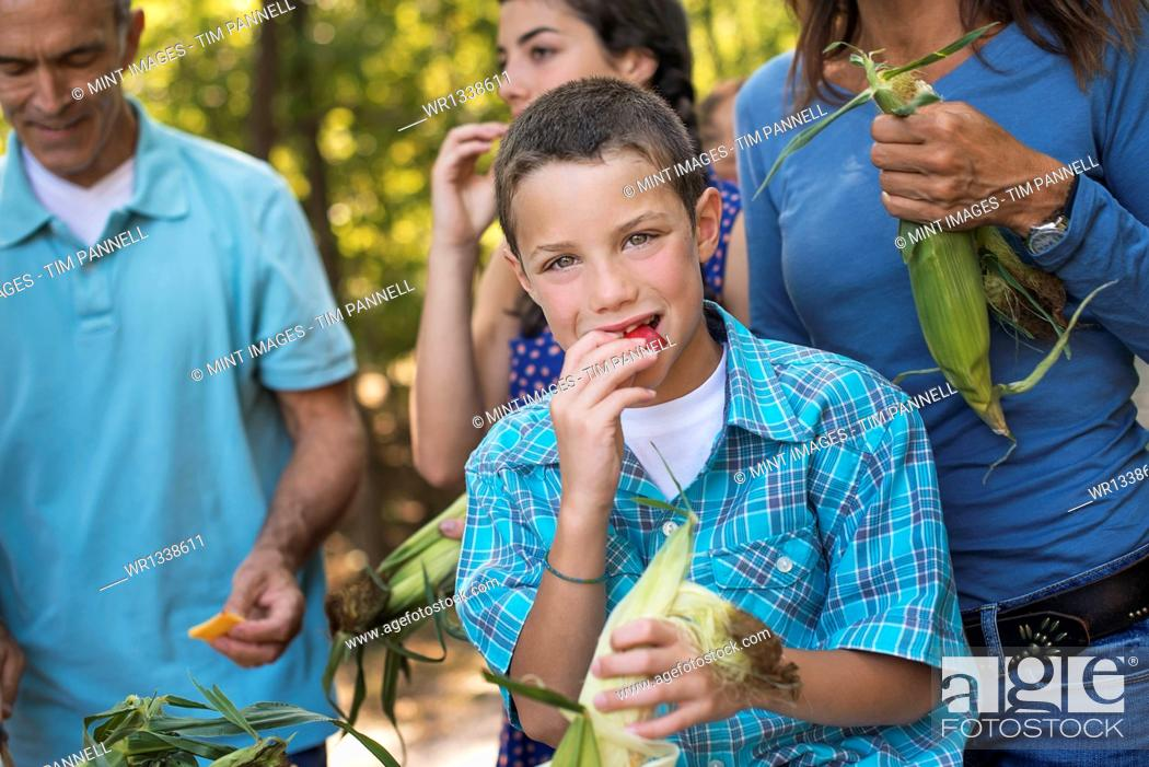 Stock Photo: A group of young people eating raw fresh vegetables, sweet corn cobs, just after picking them.