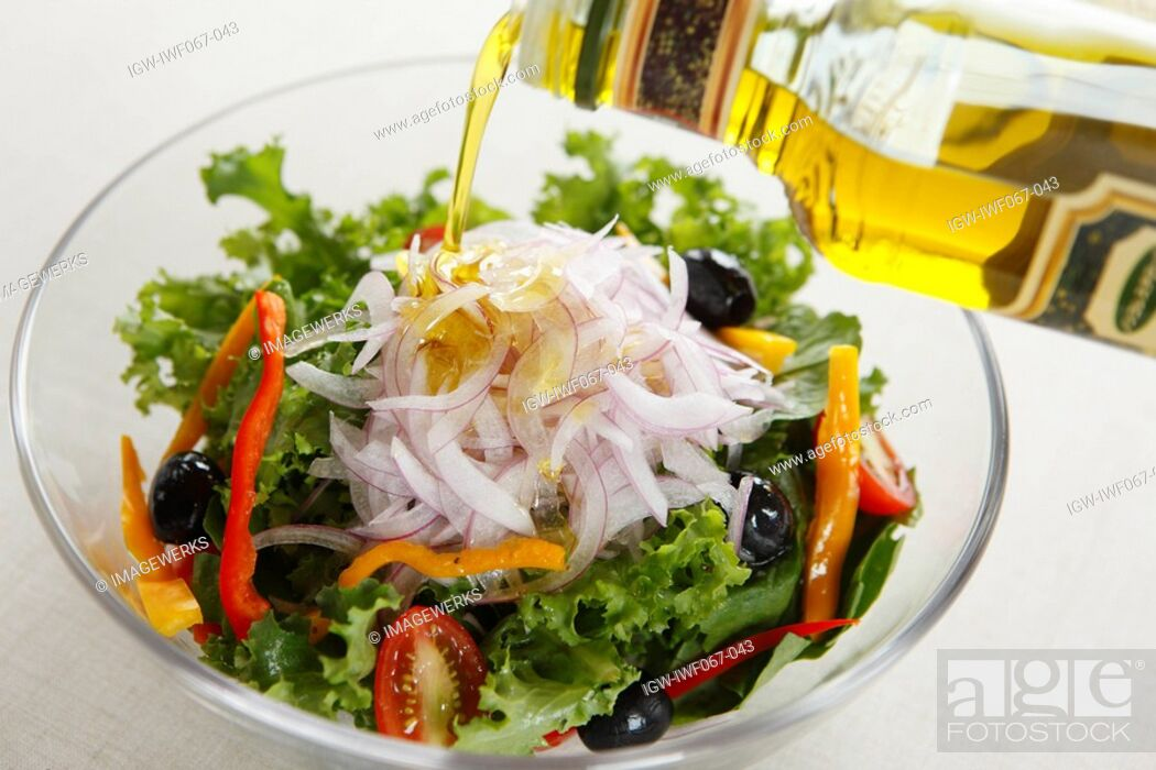 Stock Photo: Oil being poured on bowl of vegetable salad.