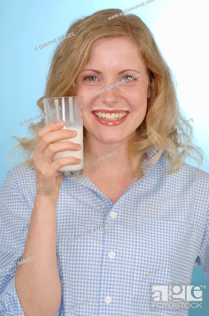 Stock Photo: Young woman drinking a glass of milk.