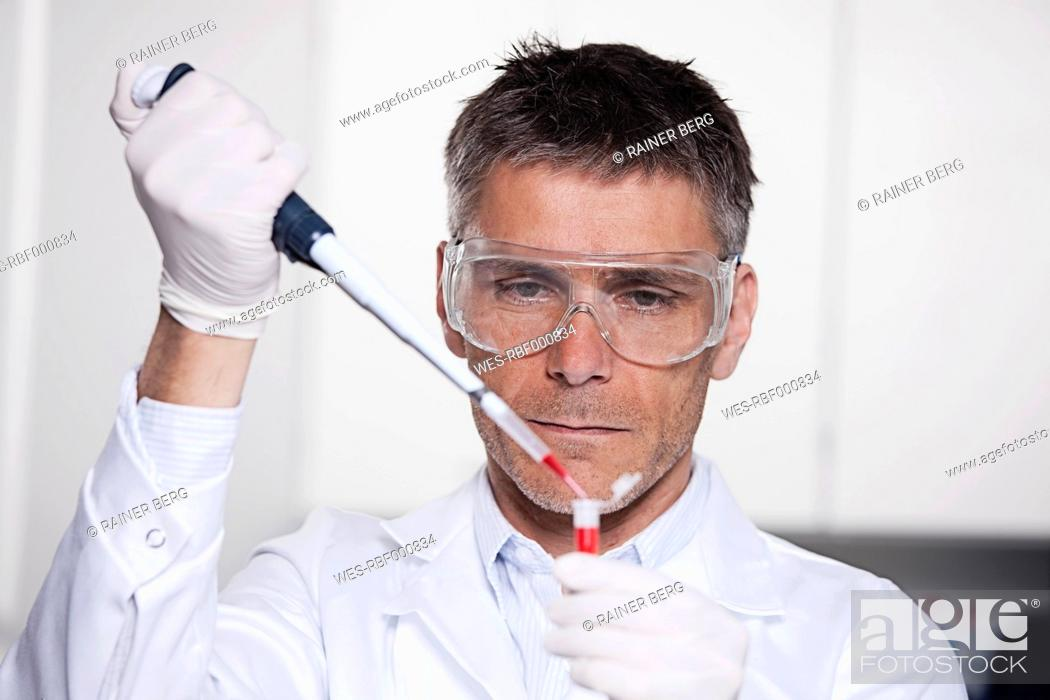 Stock Photo: Germany, Bavaria, Munich, Scientist pouring red liquid with pipette in test tube for medical research in laboratory.