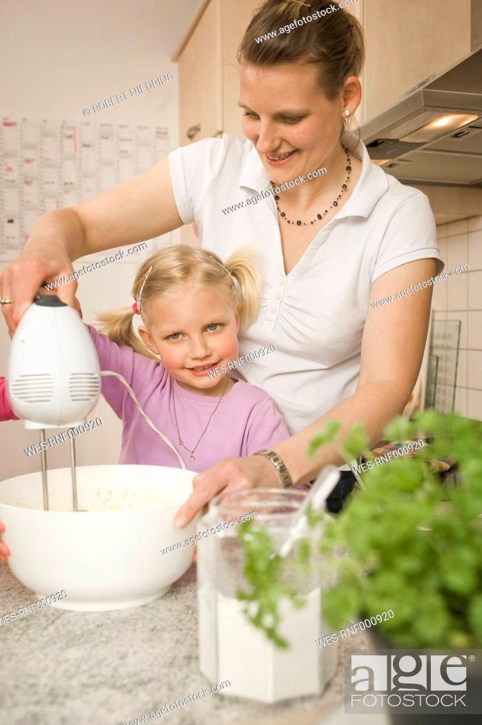 Stock Photo: Mother and daughter mixing batter with electric whisk.