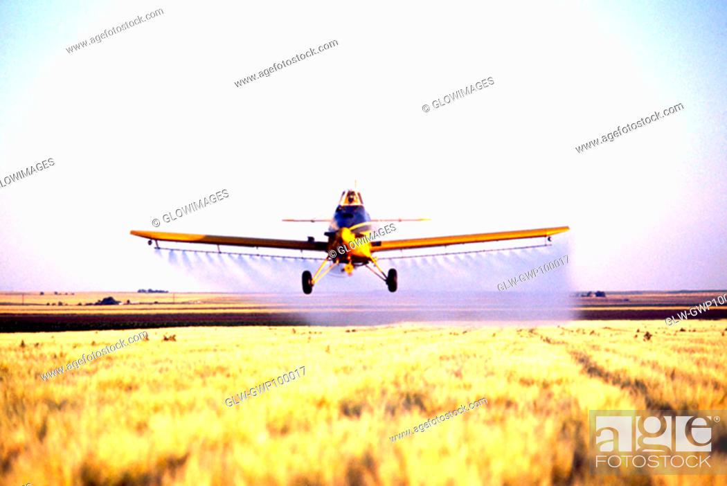Stock Photo: Plane spraying pesticide barley field in Colorado.