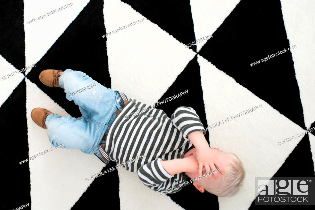 Stock Photo: Young boy lying on floor, covering eyes, elevated view.