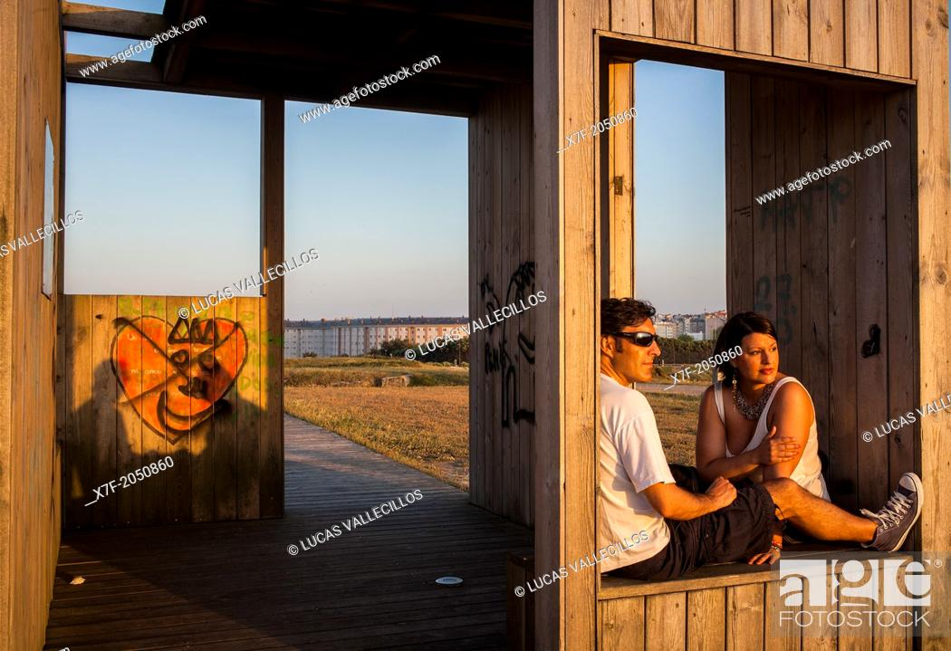 Stock Photo: Couple in huts for shelter from the wind, Punta Herminia gardens, Coruña city, Galicia, Spain.