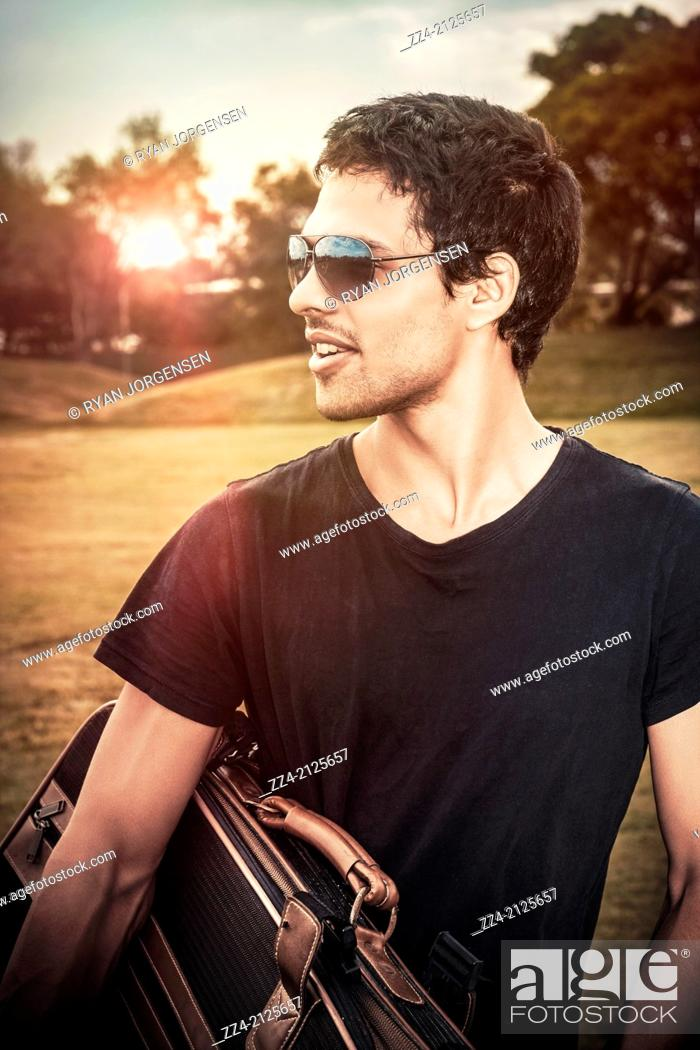 Stock Photo: Handsome young man in early 20s wearing casual fashion and sunglasses carrying suitcase while on a summer travel trip to Australia.
