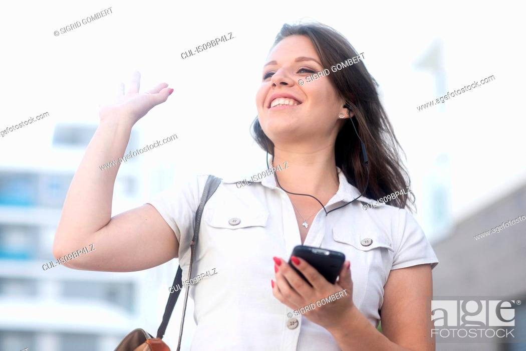 Stock Photo: Woman holding smartphone and waving.