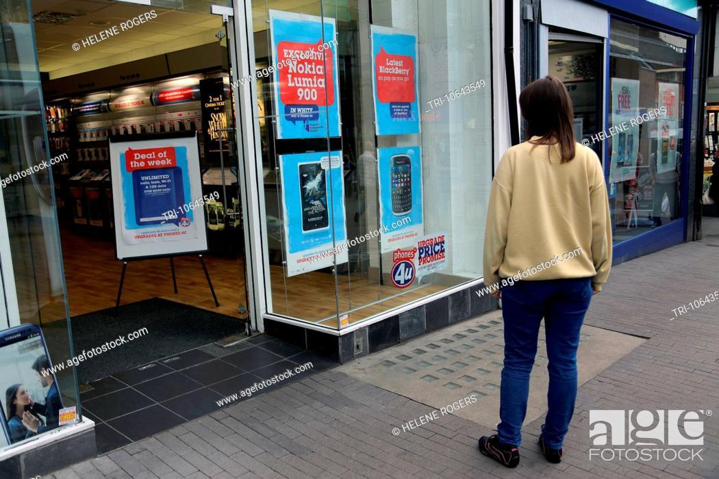 210eee4ca28 Stock Photo - Woman Looking At Mobile Phones Advertised In Mobile Phone Shop  Window Surrey England