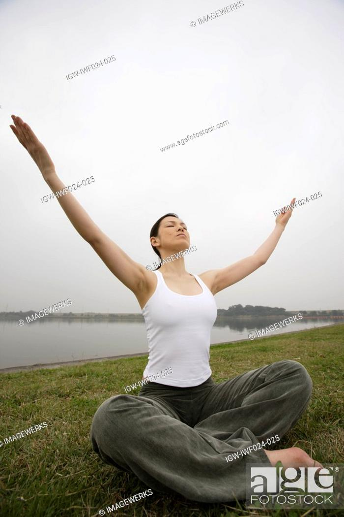 Stock Photo: Front view of a young woman in lotus position.
