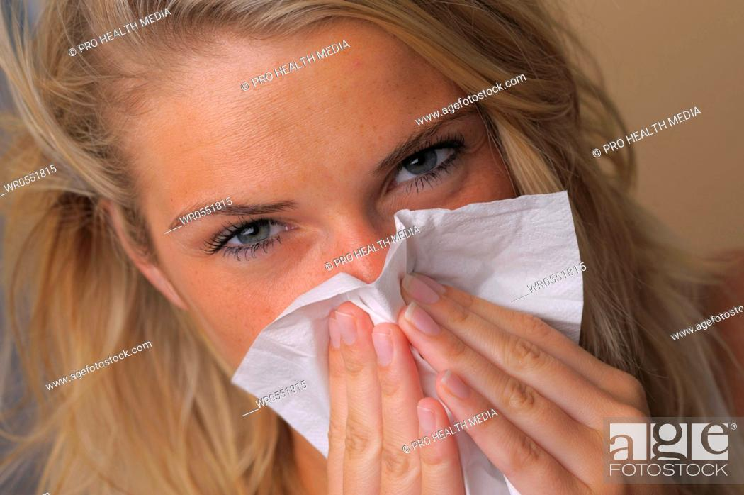 Imagen: sneezing young woman with a tissue.