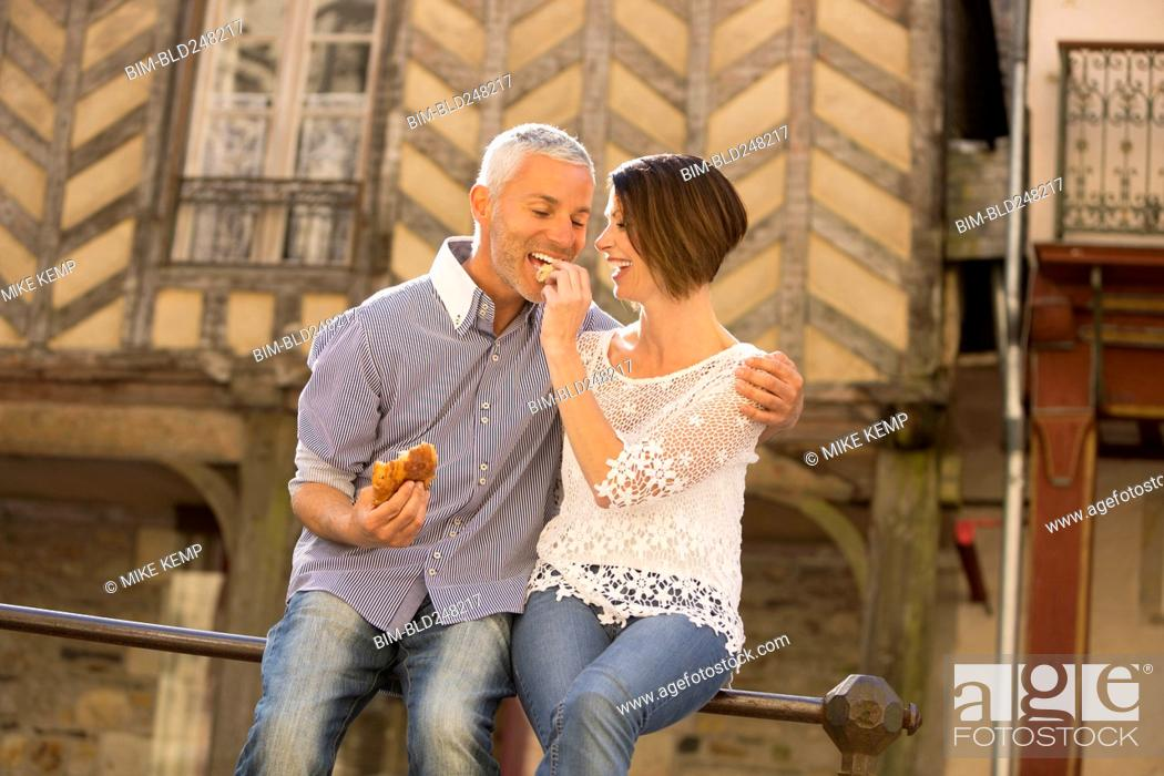 Photo de stock: Caucasian couple eating bread on railing.