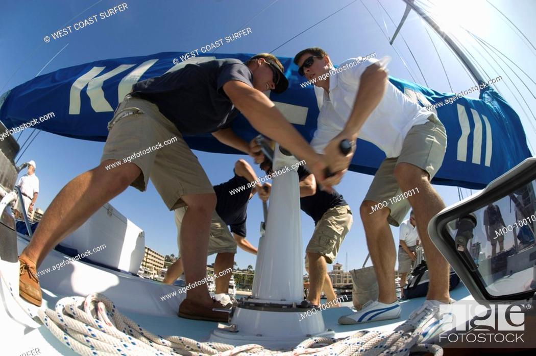 Stock Photo: Sailors operating windlass on yacht low angle view.