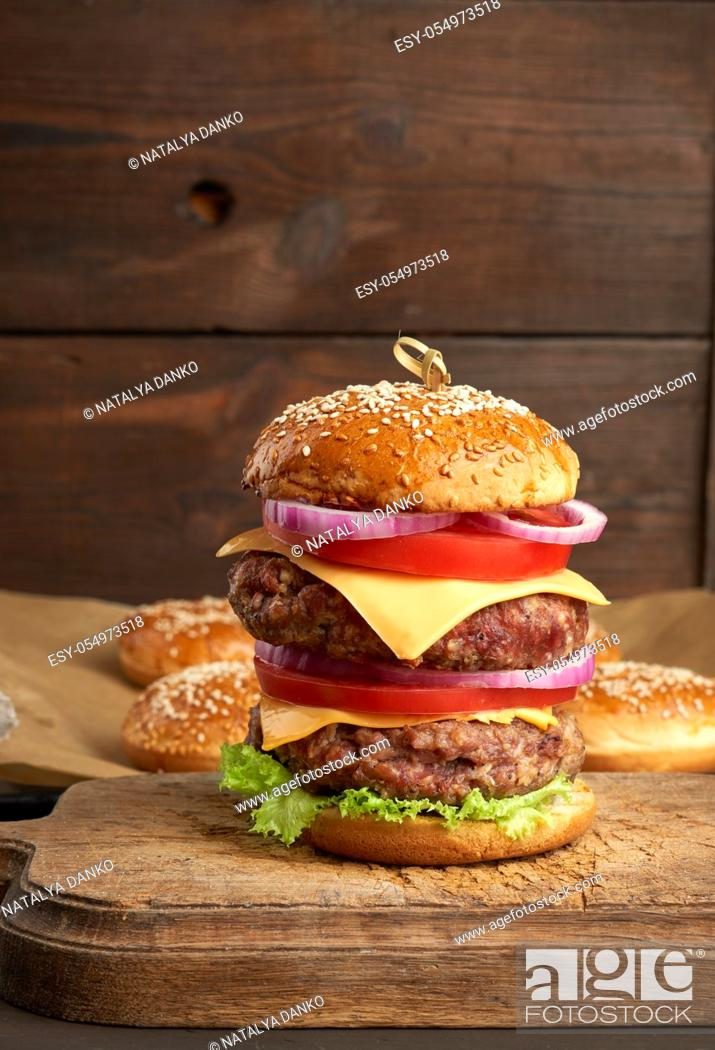 Stock Photo: double cheeseburger with tomatoes, onions, barbecue cutlet and sesame bun on an old wooden cutting board, brown background. Fast food.
