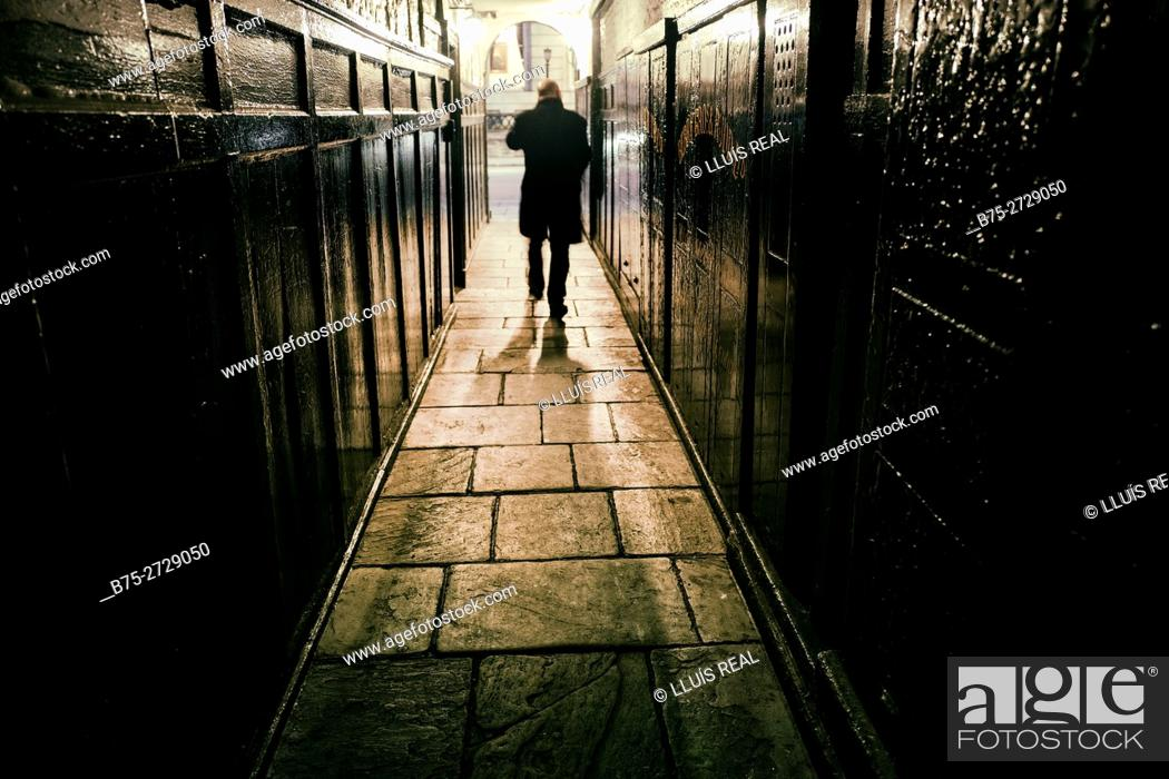 Stock Photo: Silhouette of unrecognizable man walking at night through a hallway, wearing black coat. London, England.