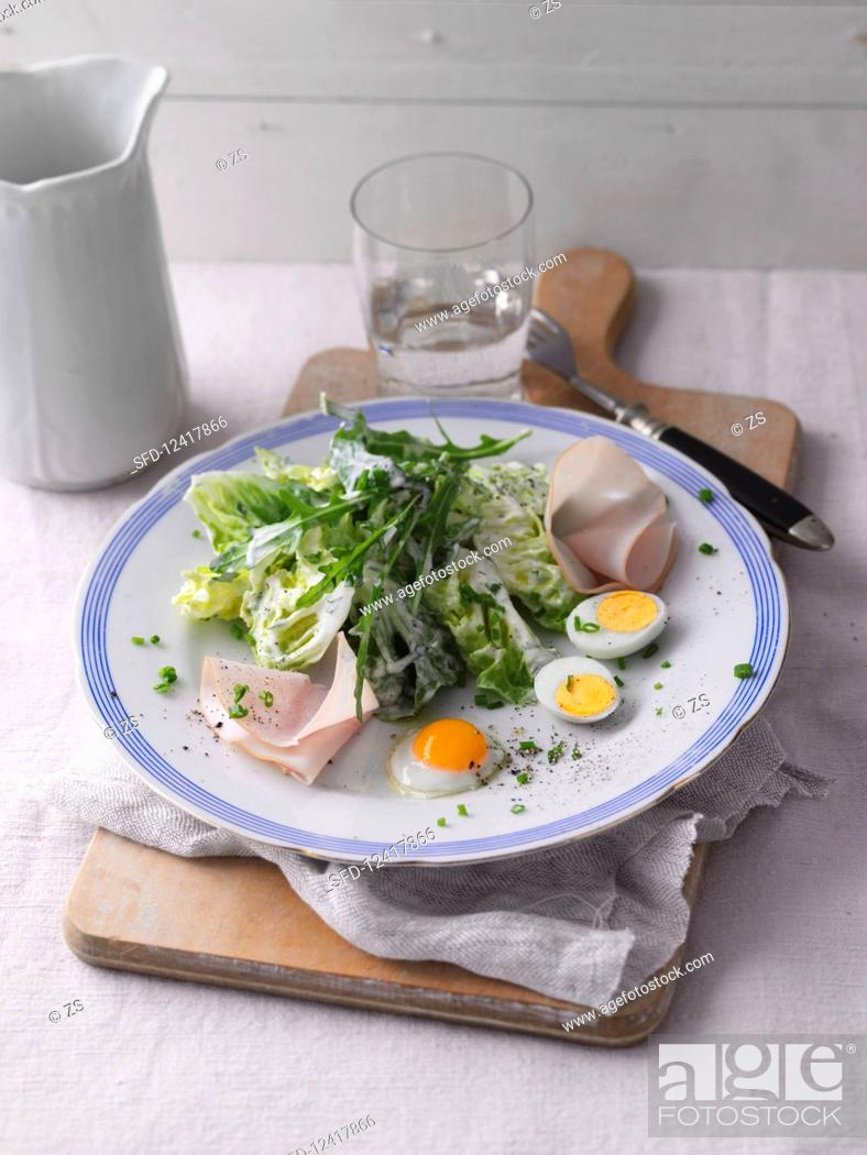 Stock Photo: A mixed leaf salad with turkey breast and quail's eggs.