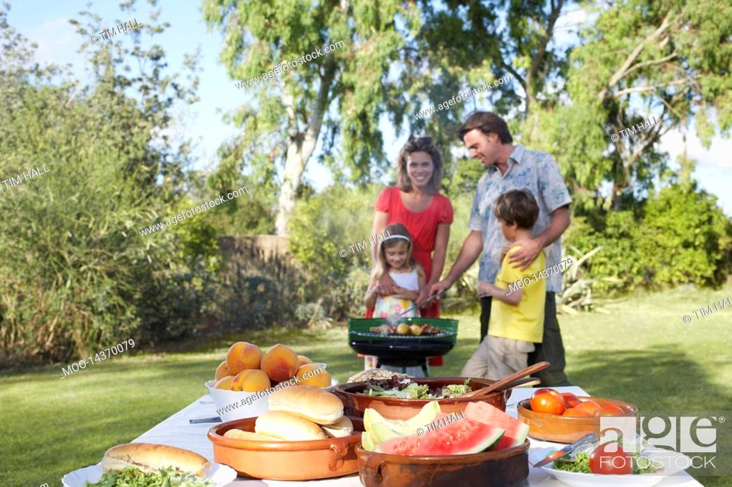 Stock Photo: Family with two children 5-6 grilling table in foreground.