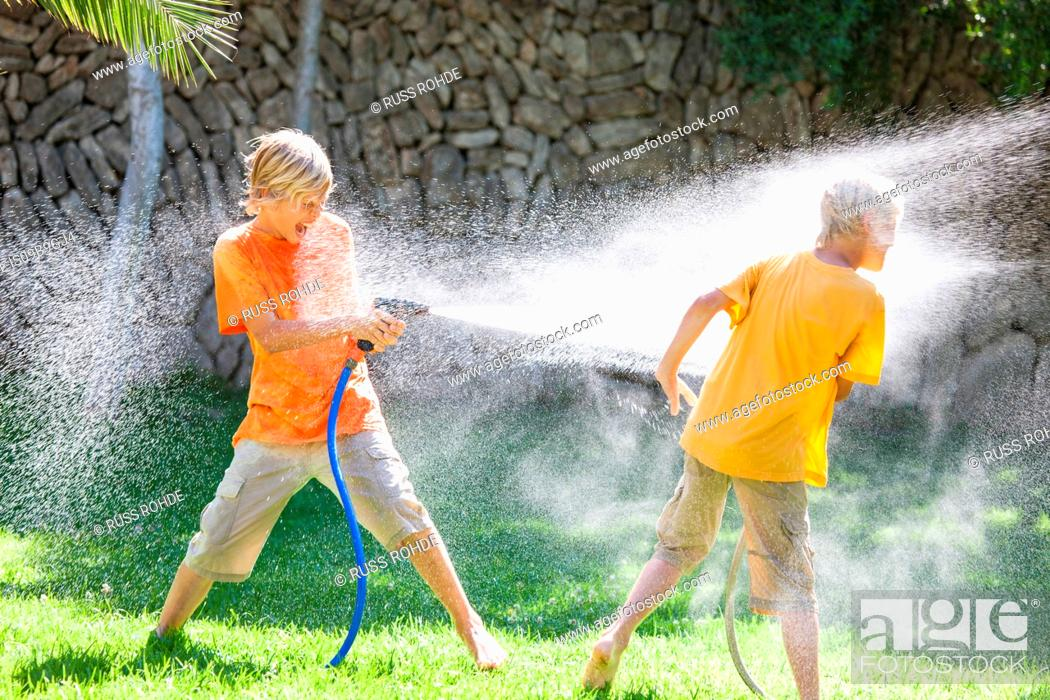 Stock Photo: Boys in garden spraying each other with water from hosepipe.