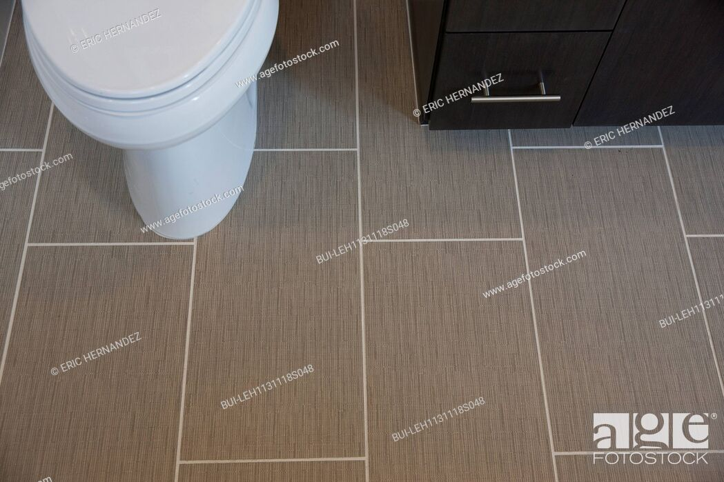 Imagen: Close-up of tiled floor with cropped commode and cabinet at home; Irvine; California; USA.