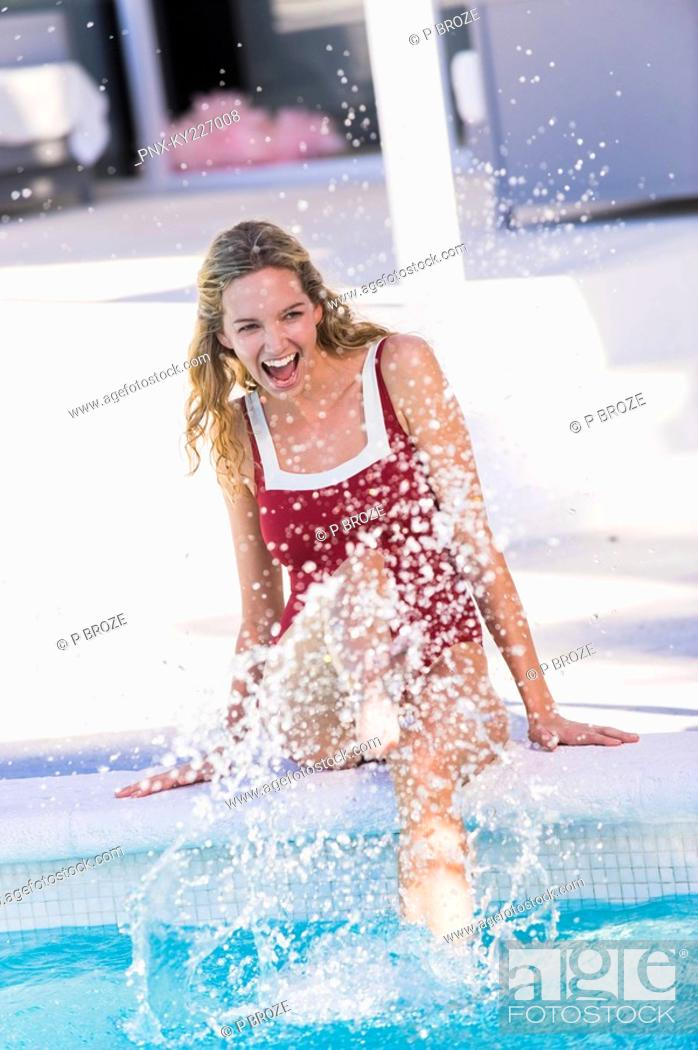 Stock Photo: Woman sitting at the poolside and splashing water.