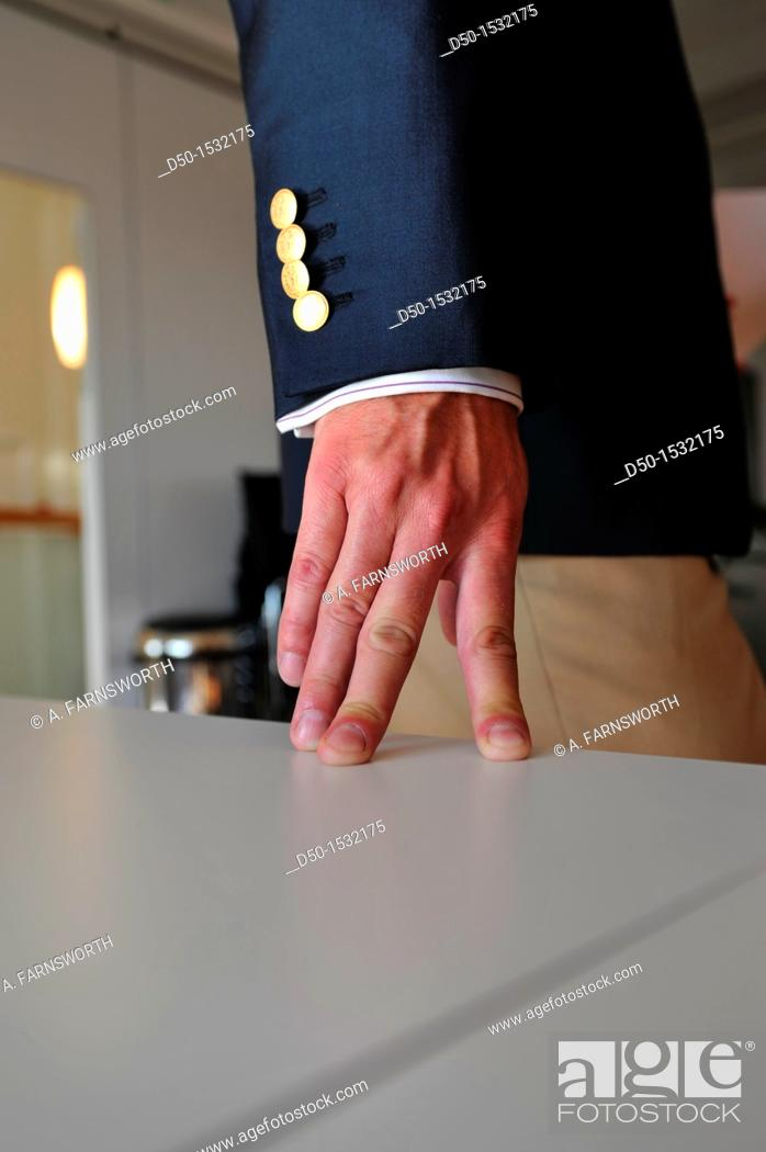 Stock Photo: Man in jacket rests fingers on table (Notice: Four button, four fingers), Stockholm, Sweden.