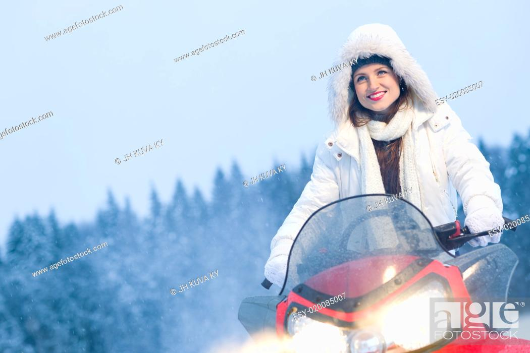 Stock Photo: Winter, beautiful woman and a snowmobile, horizon format.