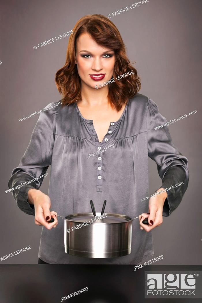 Stock Photo: Young woman holding stew pot.